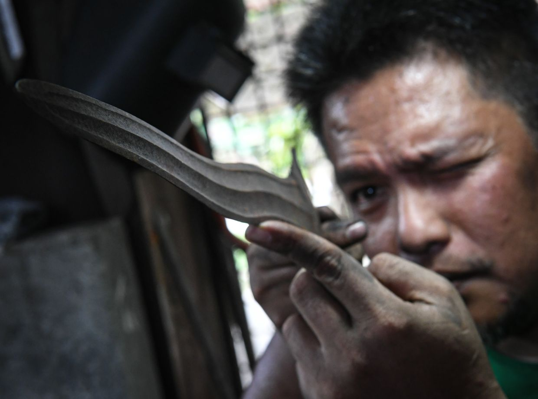 Wan Islahuddin examines the intricate details of a keris made in his workshop. Photo: Bernama