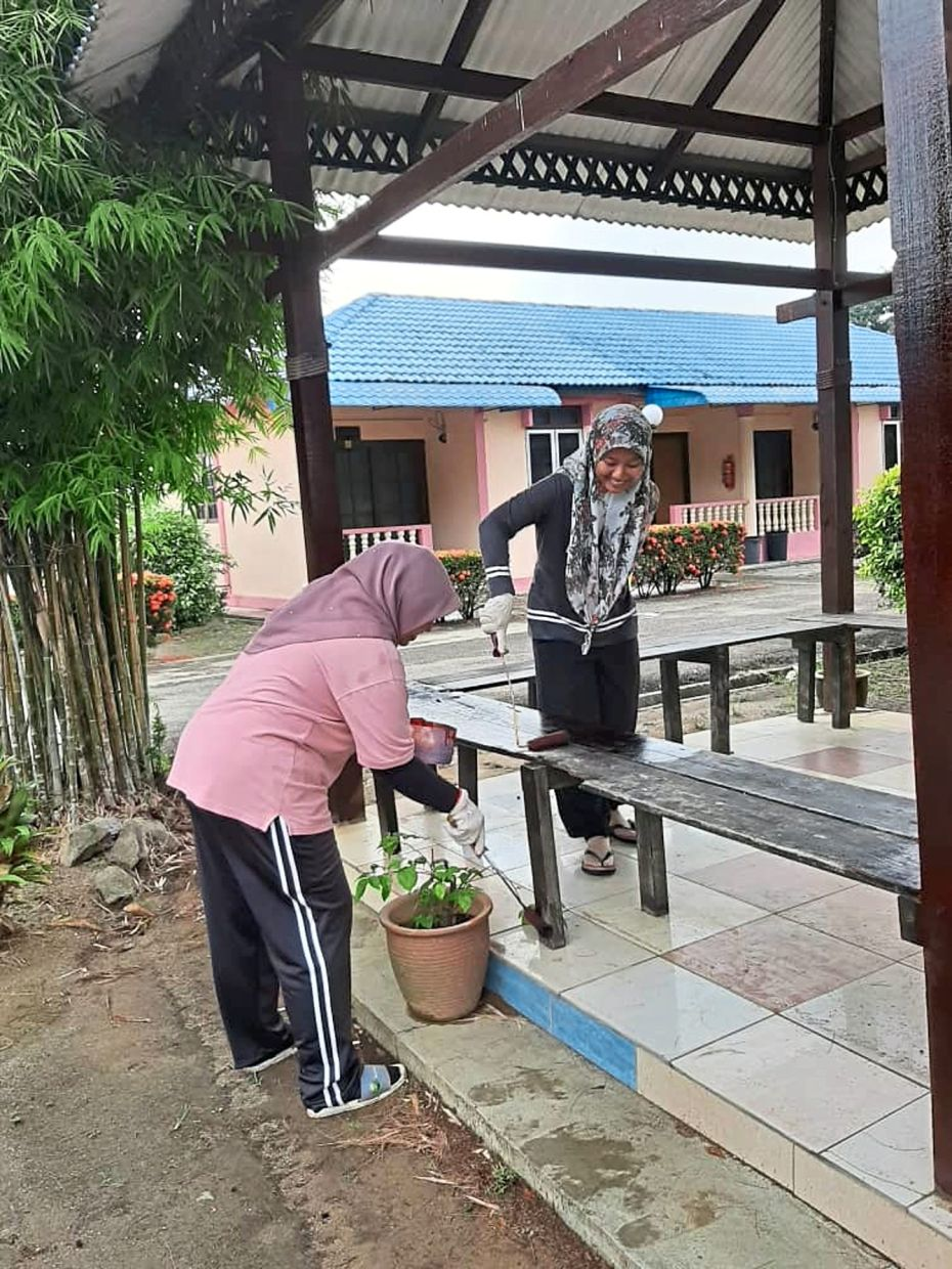 Sepang Resort employees washing and painting the benches to spruce up the place before reopening on June 20.