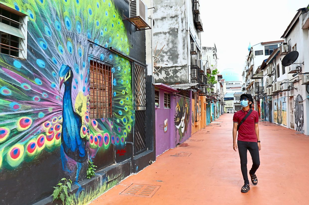 Dhiyaul walking past the mural of a peacock along a back lane off Jalan Tengku Diauddin in Klang. — Photos: FAIHAN GHANI/The Star