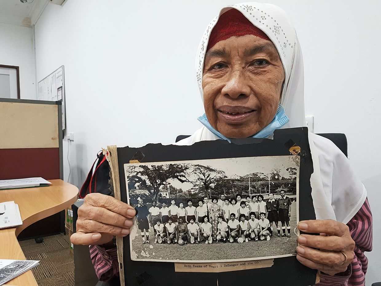 Tunku Ellie holding a photo of the Negri Sembilan Women's Football Association team with players from the Selangor Women's Football Association after their first match in January 1961.