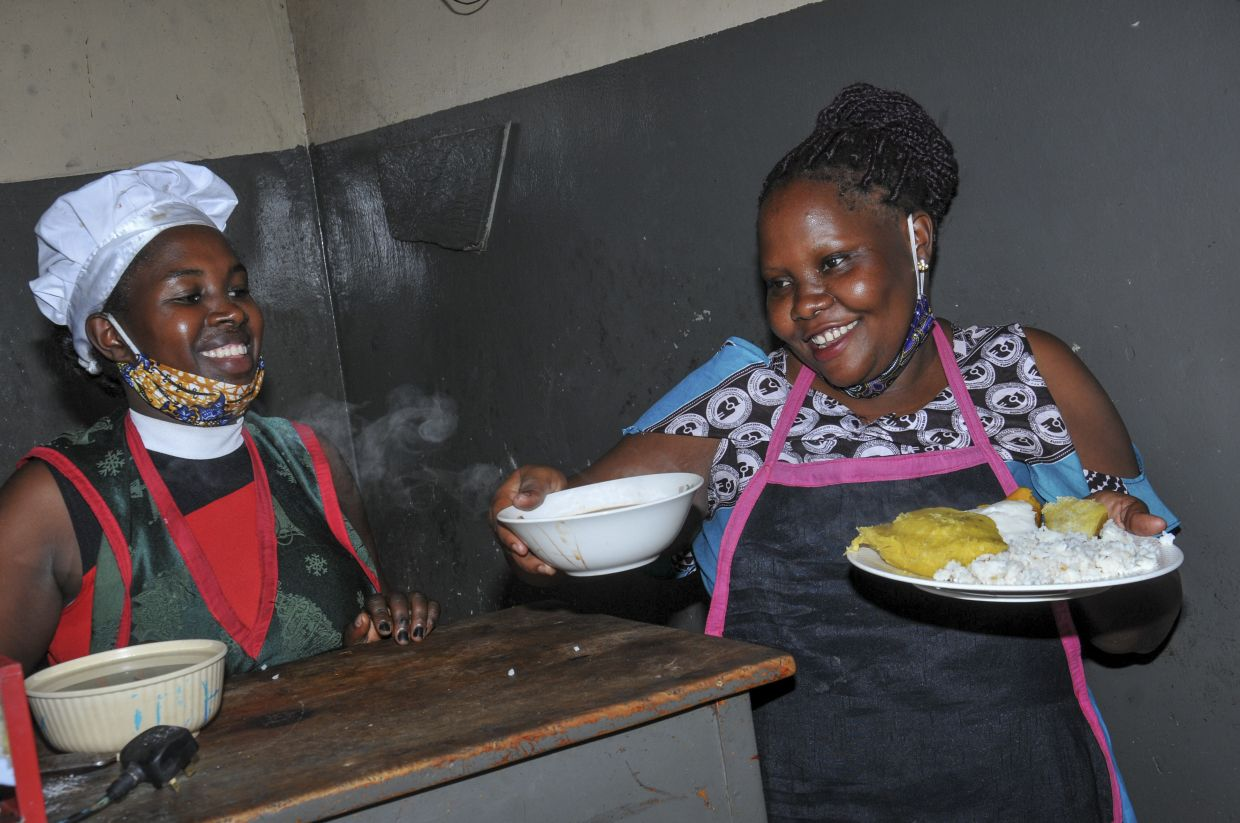 Rebecca Nakamanya, left, and colleague Namara Grace, right, worry about earning just enough to fees their children.