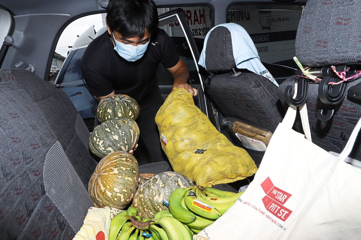 Chan loading his car with supplies to send to the poor.