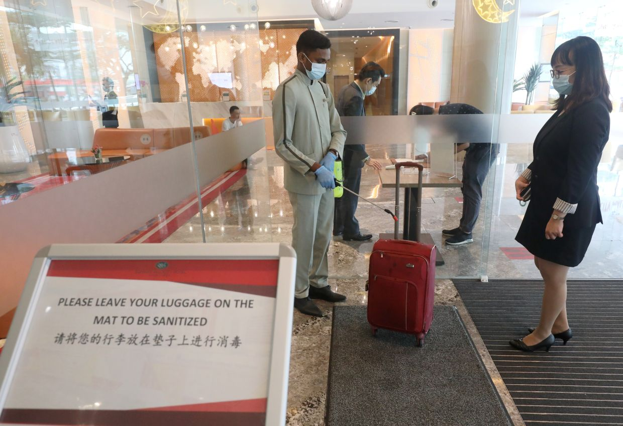 A hotel concierge sanitising a guest\'s luggage before she enters the hotel\'s lobby. The Mita virtual travel fair would be held from July 1-15. SAMUEL ONG/The Star