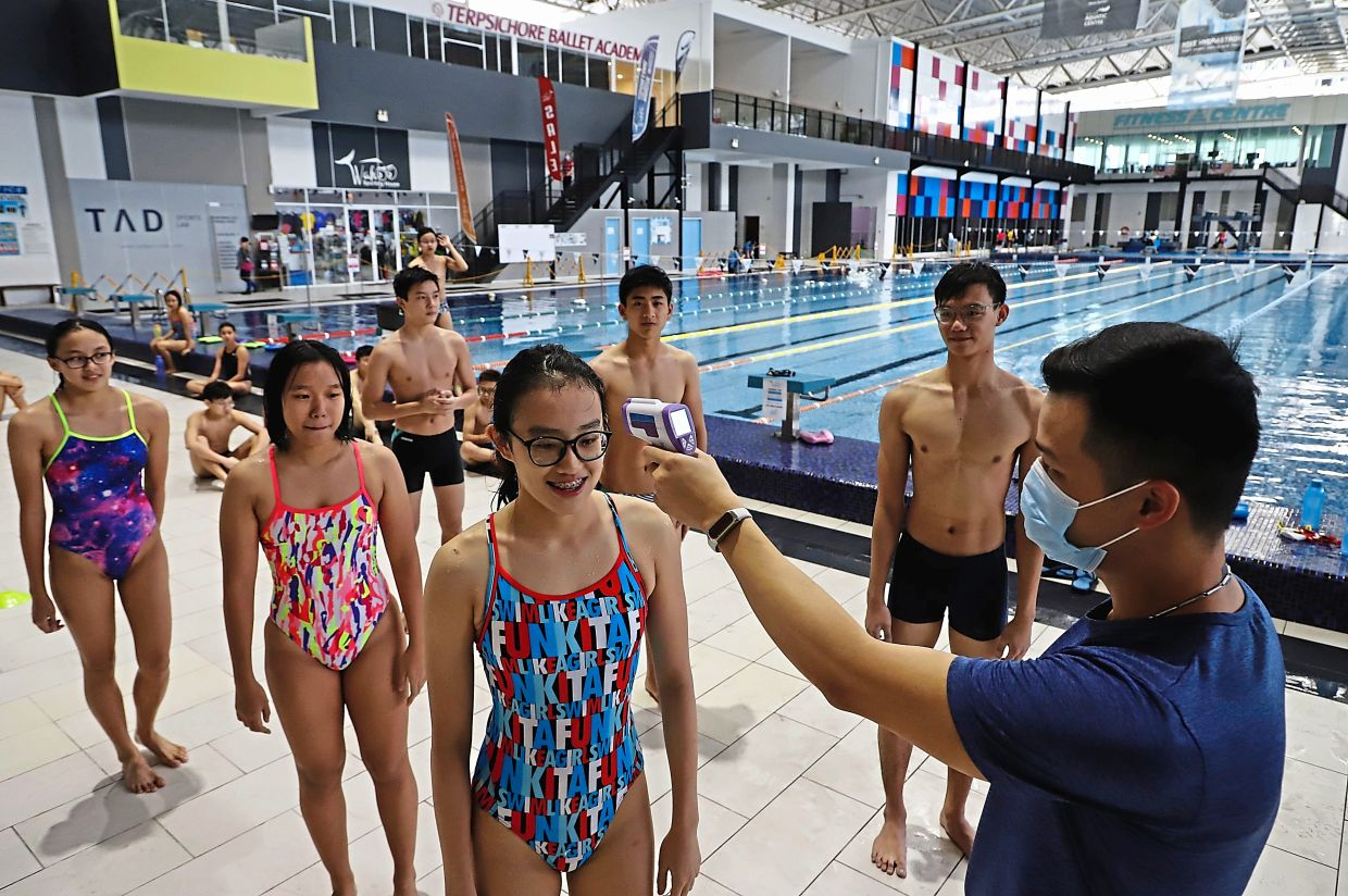 Coach Choo Wei Xiang, 32, (right) taking the temperature of swimmers before their training session.
