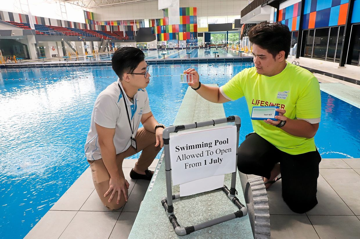 Safety inspection: Lifeguard Rafiudin Ramli, 25, showing the water quality test kit to his manager Jackson Wang at the Setia SPICE Aquatic Centre in Bayan Lepas, Penang.