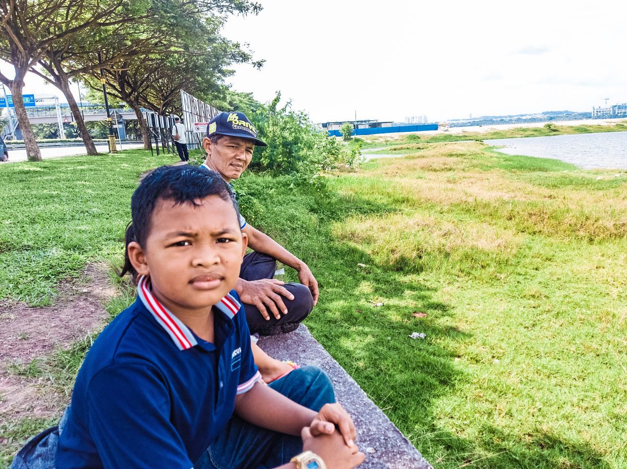Sahwali (with cap) and his son Mohd Adam, nine, enjoying the view at Pantai Lido.