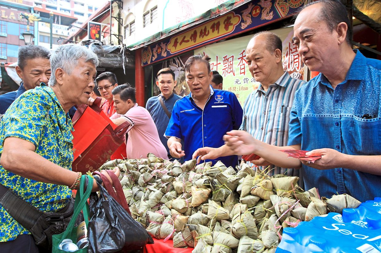 Wangsa Maju MCA chief Datuk Seri Yew Teong Look (second from right) and Petaling Street KRT president Datuk Chan Kwok Chin (third from right), who is also Fung Wong third-generation owner, handing visitors dumplings and goodie bags during a past event.