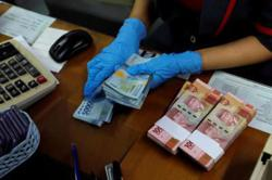Rupiah stumbles as rate cut looms, baht eases on budget gap