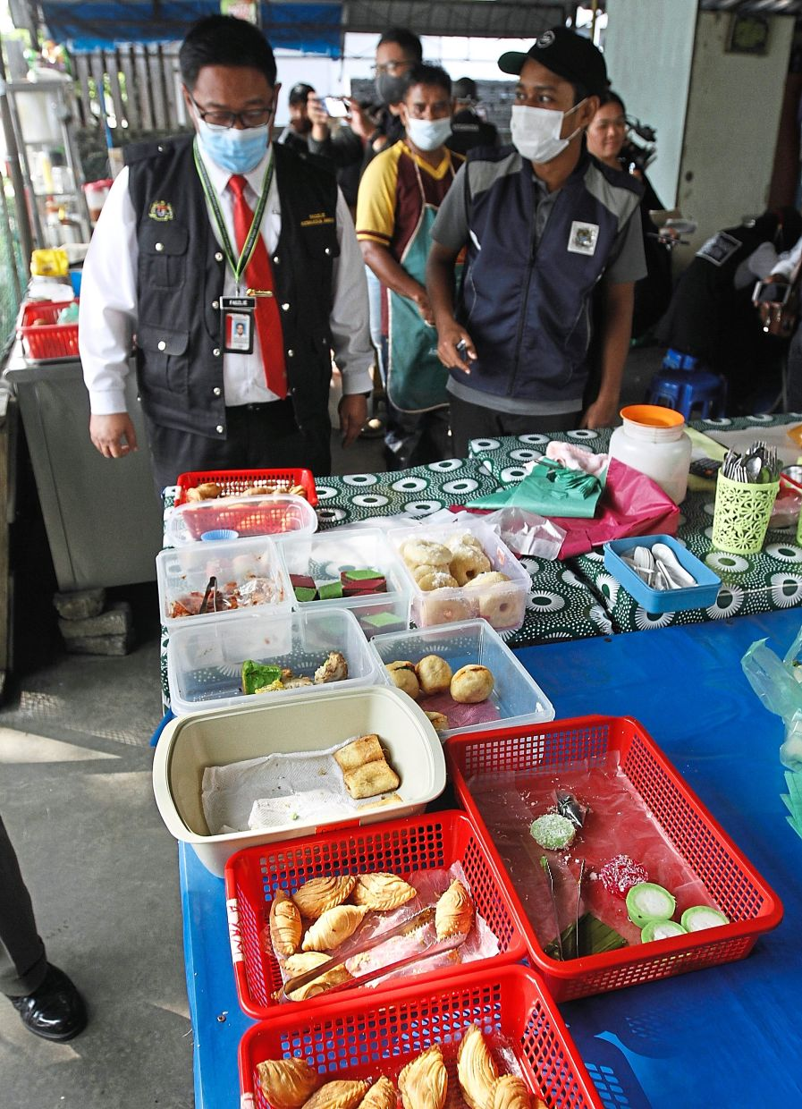 Officers noticing that food is left exposed at the roti canai stall run by the Rohingya refugee. — Photos: ZHAFARAN NASIB/The Star