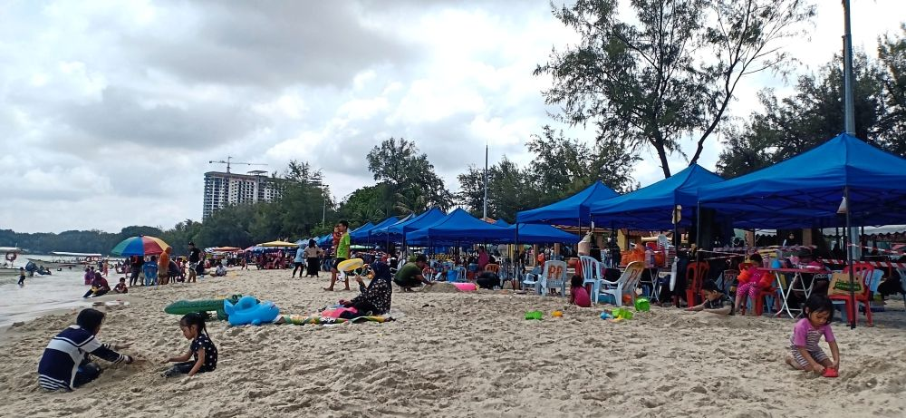Risky business: These makeshift tents along Telok Kemang provide shelter from the scorching heat but some visitors complain that they also prevent them from enjoying the view. — FARID WAHAB/The Star