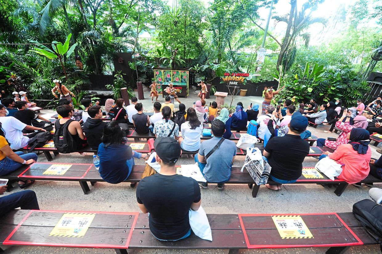 Visitors observing social distancing while watching a show at Sunway lagoon on the first day of its reopening.