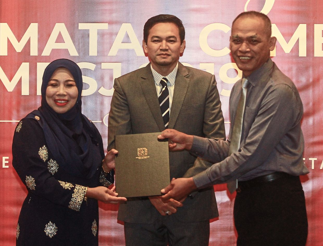 Safuan (right) receiving his long-service certificate from Noraini as Mohd Zulkurnain looks on.