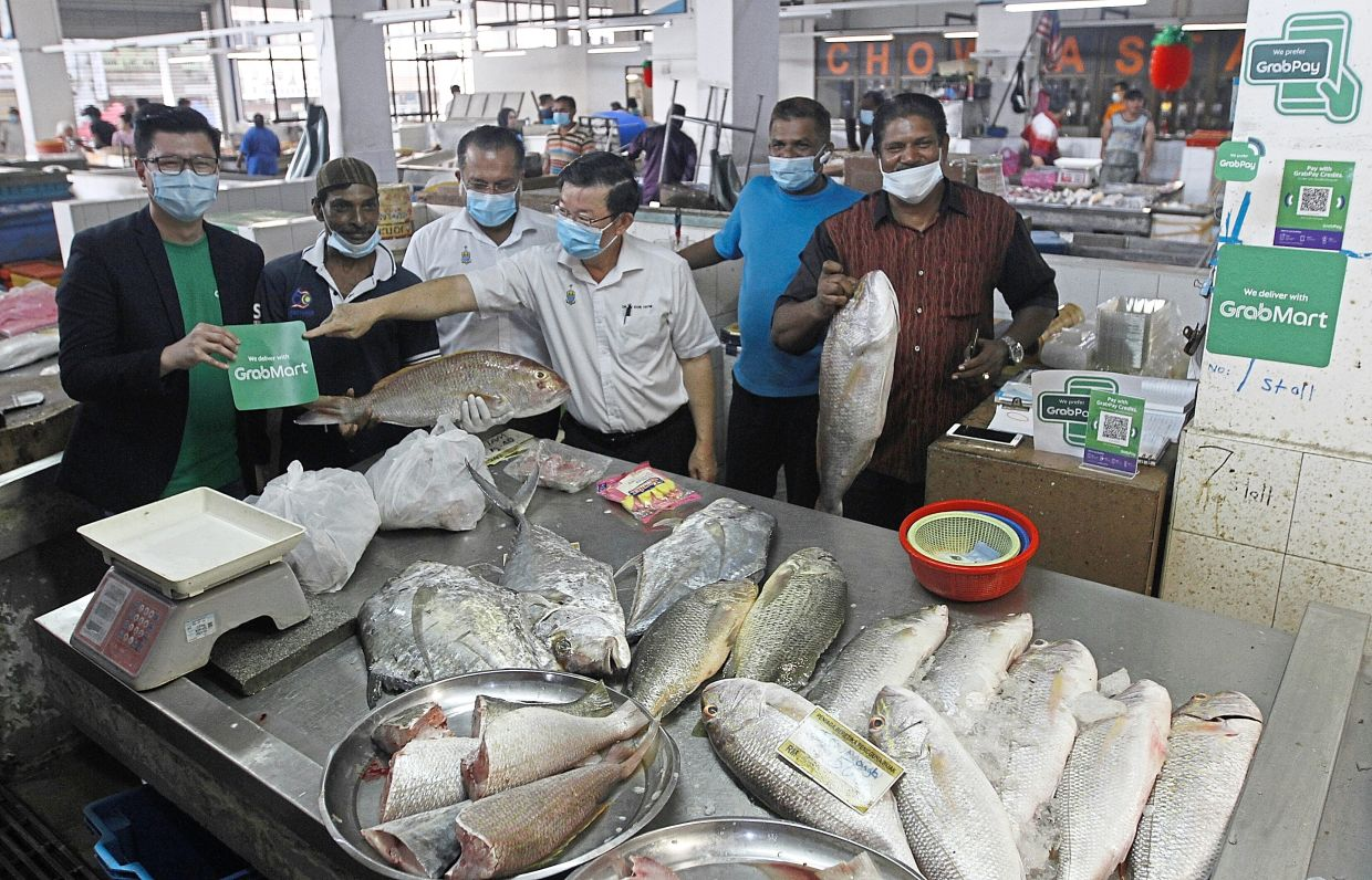 Chow (third right) visiting a fish stall at Chowrasta Market that joined the GrabMart programme.