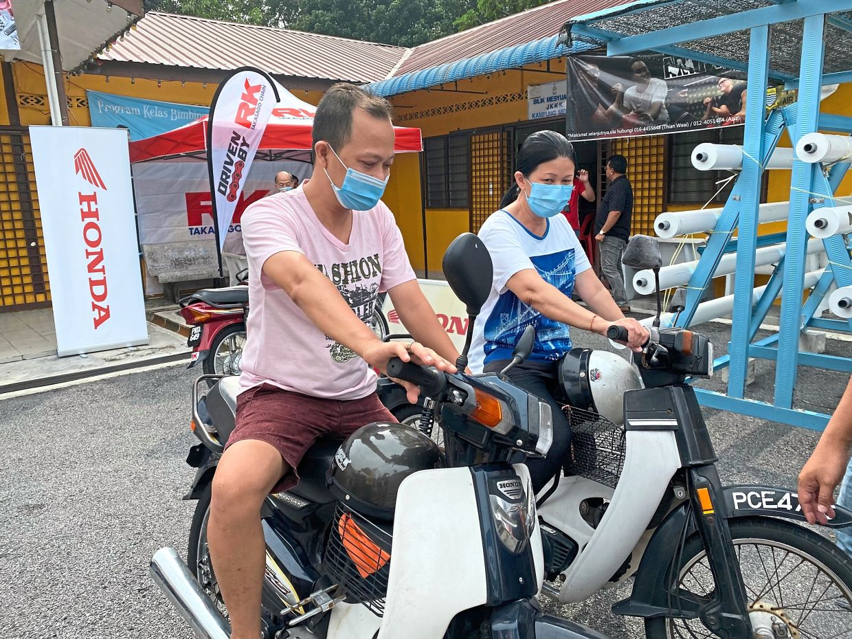 (From left) Cheah and Ng ready to ride off after getting their bikes serviced for free.