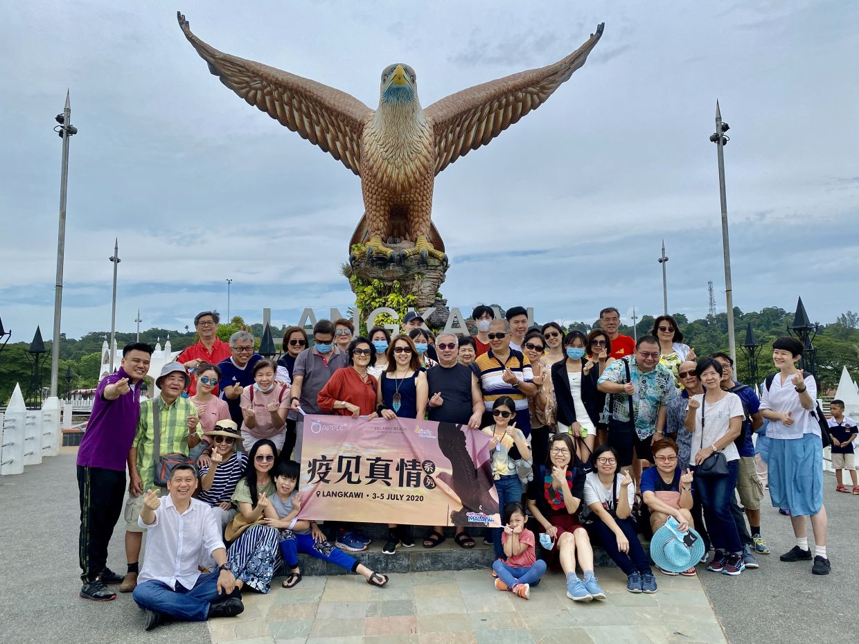 A group of 44 holidaymakers who were brought by travel agency Apple Vacations posing in front of the eagle statue at Dataran Lang in Langkawi on Sunday. They came for a three-day trip to the island. Apple Vacations group executive director Datuk Seri Lee San said two coaches were hired for the group to ensure social distancing is maintained.