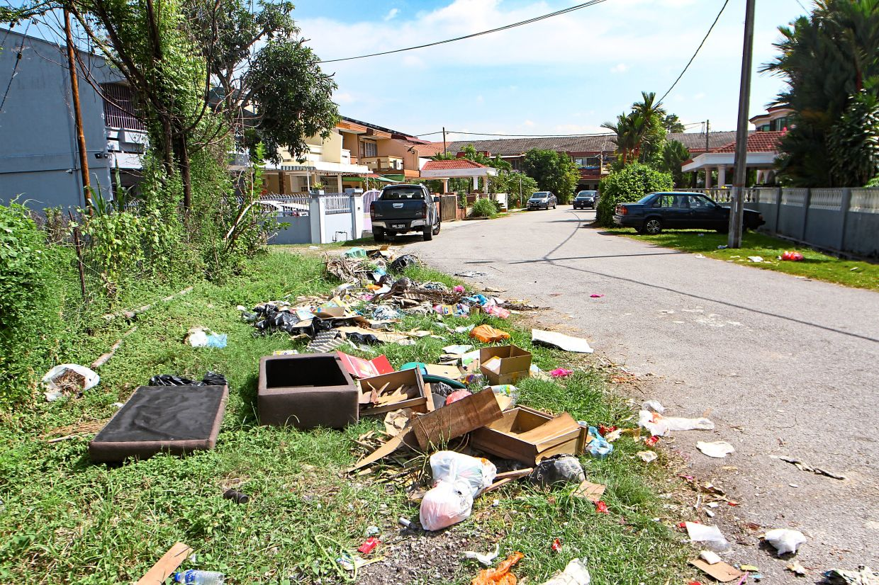 Broken wooden furniture and other rubbish dumped on the side of Jalan Dato Amar in Taman Setia, Klang.