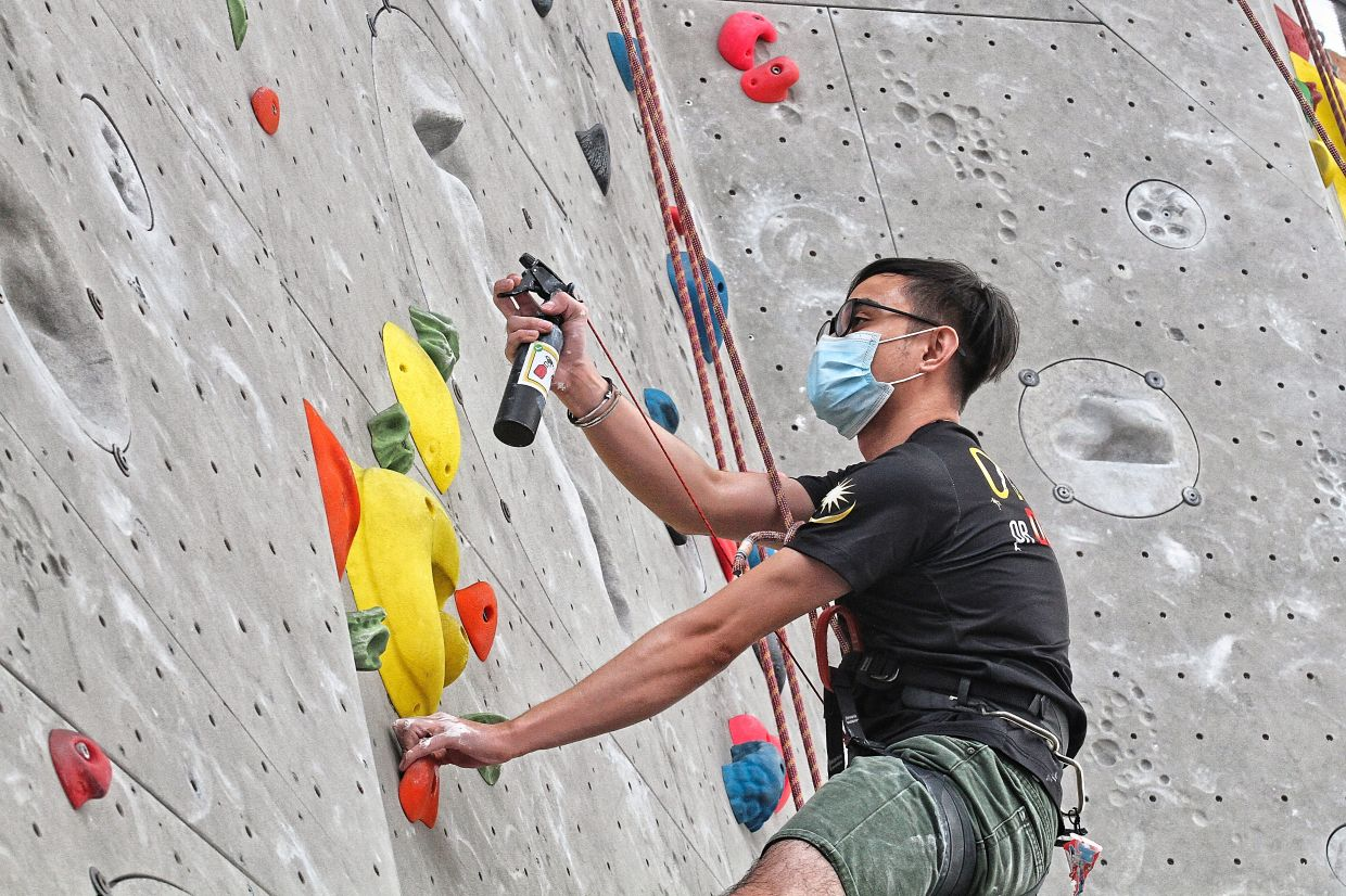 Climbers can hook sanitisers to their harnesses and spray the holds when they make their way down the wall at Camp5.