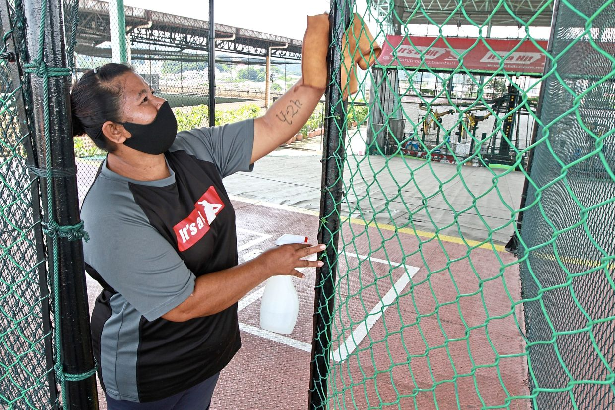 A worker sanitising the premises at It's a Hit rooftop baseball pitch in Petaling Jaya.