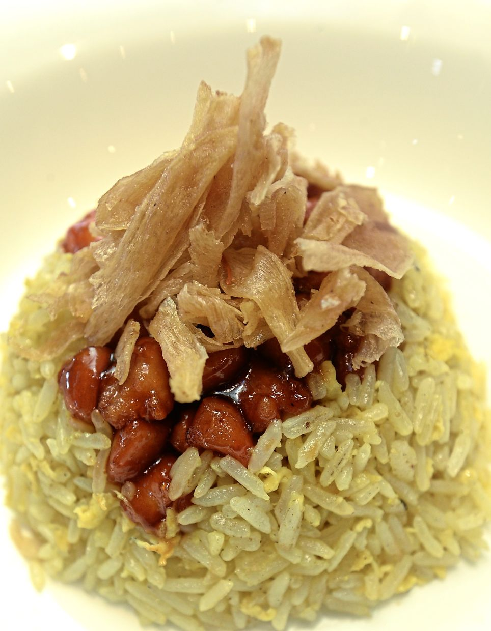 Wok-fried rice served with tangy, sweet and salty honey chicken topped with crispy paper-thin slices of candied ginger.