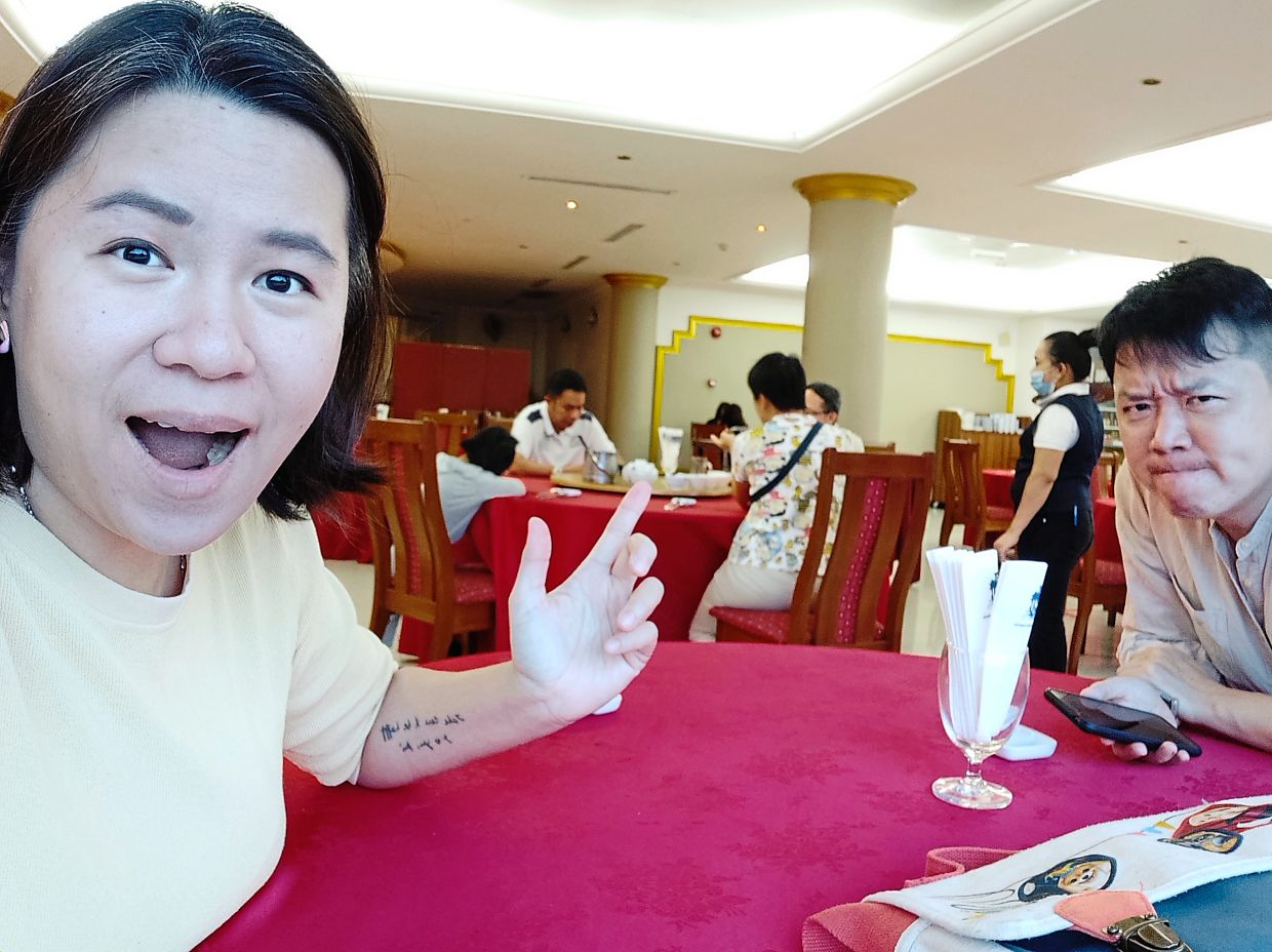 Yan (left) was upset as she and her husband Adrian Tan (right) were seated at a different table from her sister and family (pictured sitting at the table behind them). — YAN LAI PEEN