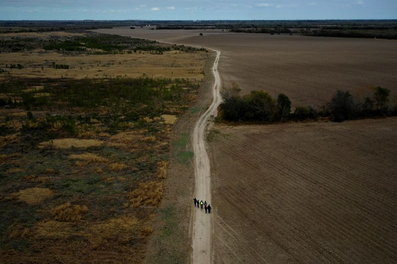 FILE PHOTO A group of migrants walk past plowed farmland after crossing into the United States from Mexico as they make their way towards a gap in the border wall to surrender to US border patrol near Penitas Texas U.S. January 10 2019. REUTERSAdrees LatifFile Photo
