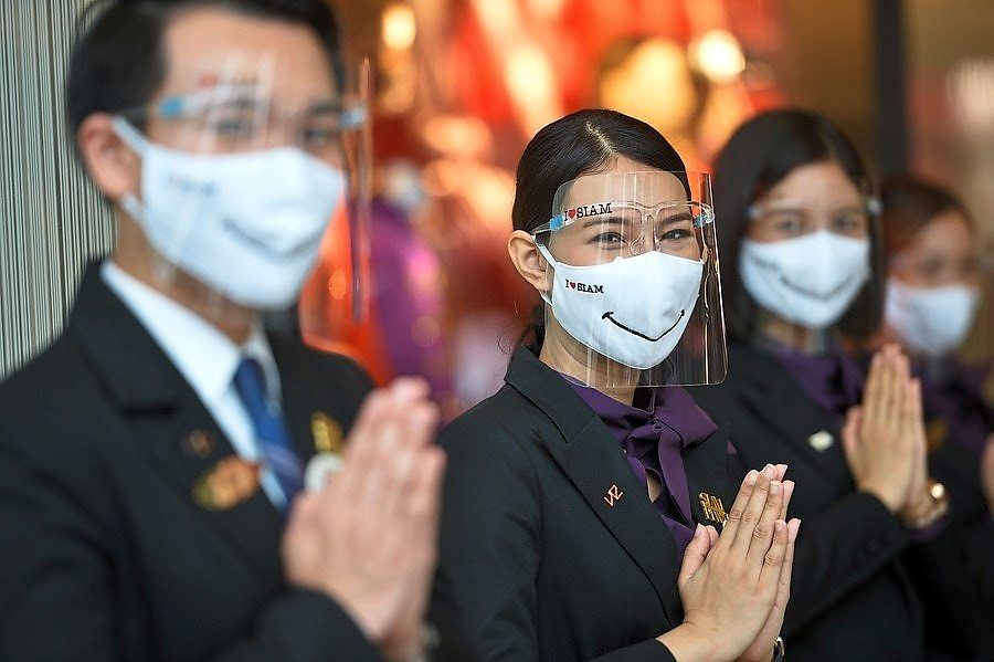 Changing landscape: Workers welcome customers at a shopping mall in Bangkok. Thailand is mulling reopening its door to international tourists through travel bubbles. — Xinhua
