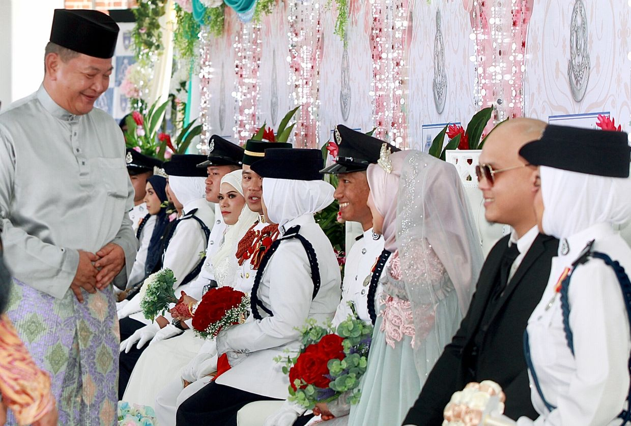 His staff's welfare is close to his heart. Here Abdul Hamid (standing) is having a light moment with newlyweds after a mass wedding ceremony for police personnel held in 2019. — Filepic/The Star
