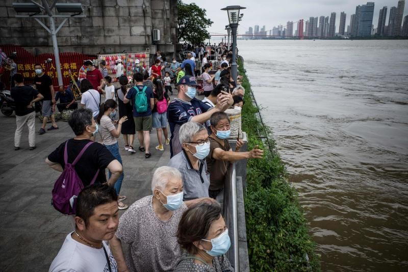 Residents looking at the swollen Yangtze River in Wuhan in China's central Hubei province. - AFP
