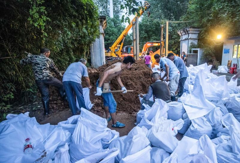 Workers preparing anti-flood measures at a gate of a park along the Yangtze River in Wuhan in China's central Hubei province. Various parts of China have been hit by continuous downpours since June. - AFP