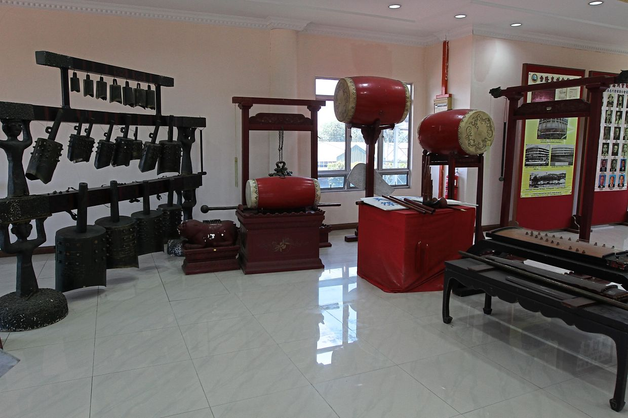 Artefacts and old photos of different clans on display in the museum at Kwong Tong Cemetery.