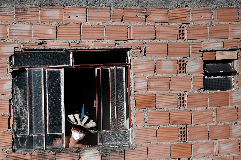 A Pataxo Ha-ha-hae tribesman at the window overlooking the favela or slum neighbourhood. Photo: AFP/Douglas Magno