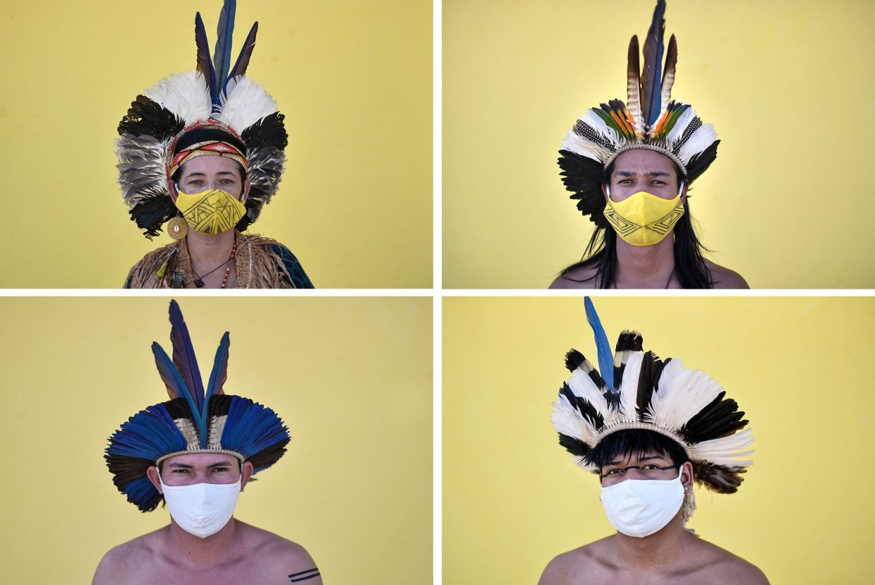(Clockwise from top left) Angoho, her husband Hayo, and tribe members Hatxotxay and Juari, in their tribal costumes and wearing face masks. Photo: AFP/Douglas Magno