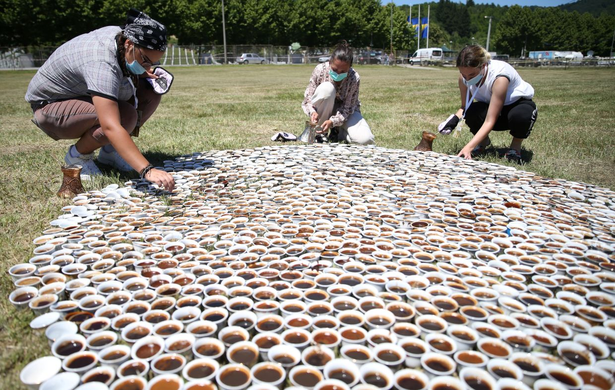 Sehovic (centre) helps install her collection of some 8,000 traditional ceramic cups filled with Bosnian coffee at the Potocari-Srebrenica Memorial Centre for victims of the 1995 massacre of Muslim men and boys by Serb forces, in eastern Bosnia. Photo: Reuters