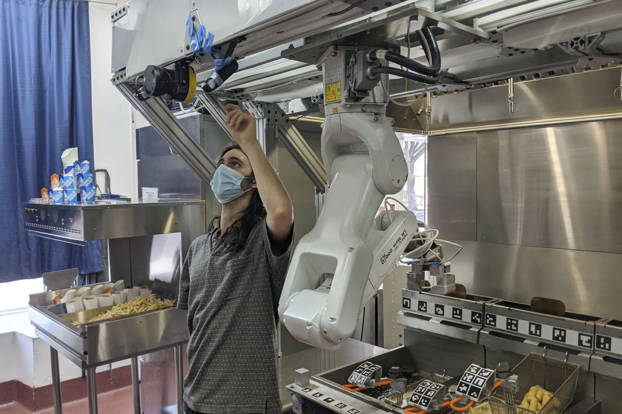 A technician makes an adjustment to a robot at Miso Robotics' White Castle test kitchen in Pasadena, California. Robots that can flip burgers, make salads and even bake bread are in growing demand as virus-wary kitchens try to put some distance between workers and customers. — Miso Robotics/AP