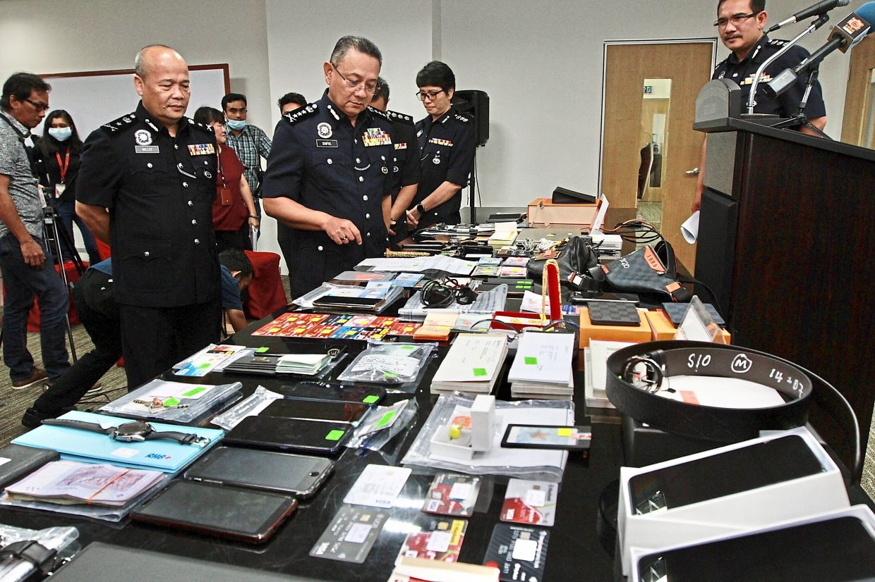 Tools of the trade: Comm Saiful (second from left) with deputy CCID director (intelligence and operations) SAC Willey Richard looking at some of the items seized at the federal CCID headquarters.