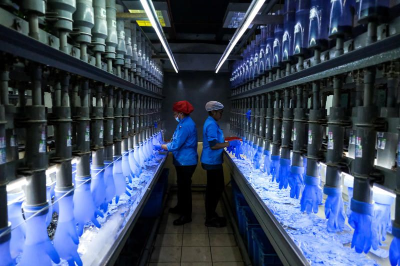 Employees check latex gloves in the watertight test room at a Top Glove Corp. factory in Setia Alam, Selangor, Malaysia. - Bloomberg