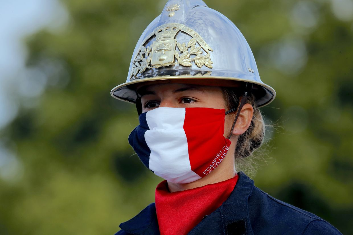 A firefighter wears a face mask with the colours of the French flag in Paris.