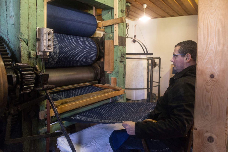 Czech craftsman Jiri Danzinger works with a rolling press at his blueprint workshop. Photo: AFP