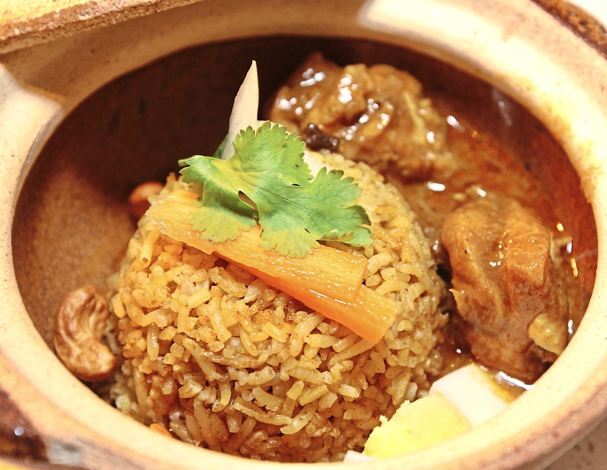 Nook's Legendary Briyani Gam is served in a mini claypot with cashew nuts.