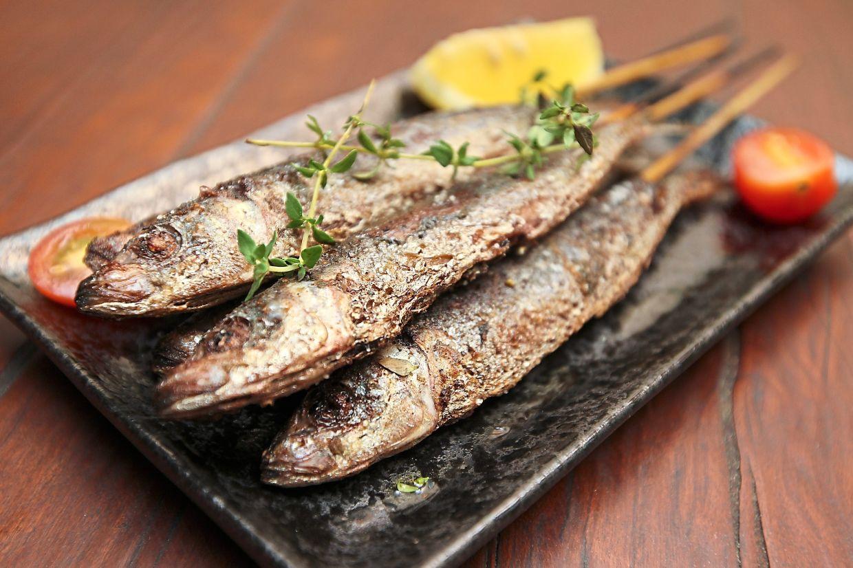 Marinated pan-fried sardines with lemon on the side.