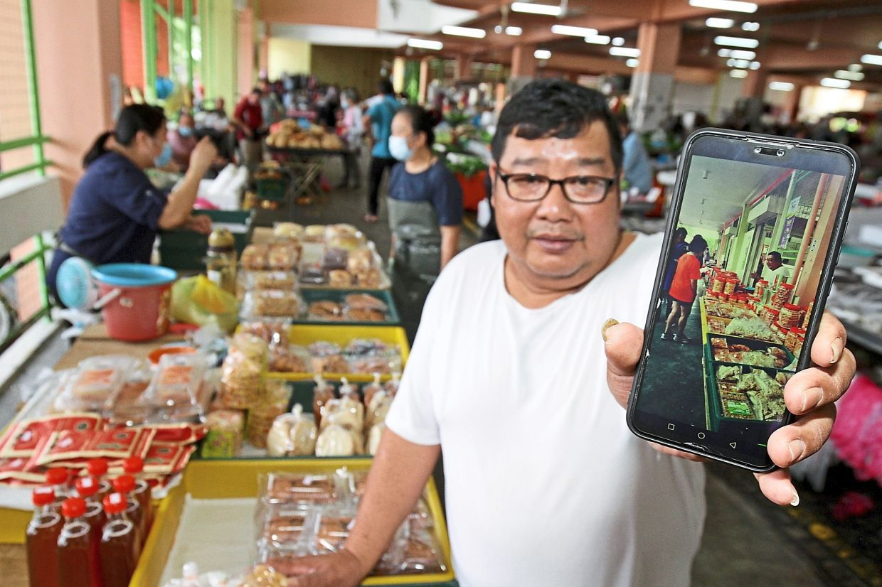 Chang showing a  picture of his stall when it was previously located at the corridor of   the Tanjung Bungah  market food court.