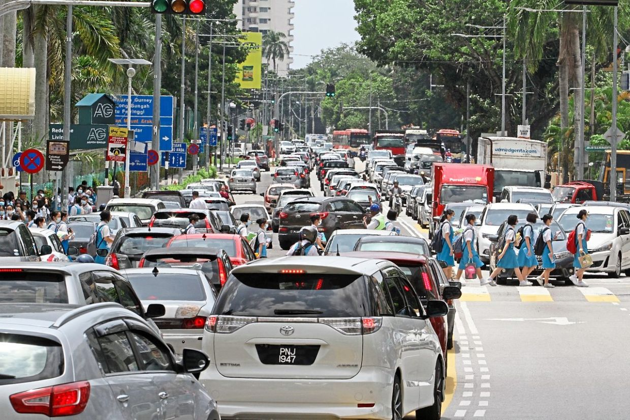 Heavy traffic: Penang Chinese Girls High School students crossing the road after school at Gottlieb Road. With the reopening of schools, traffic jam has increased in George Town, especially in the morning and after 5pm. — CHAN BOON KAI/The Star