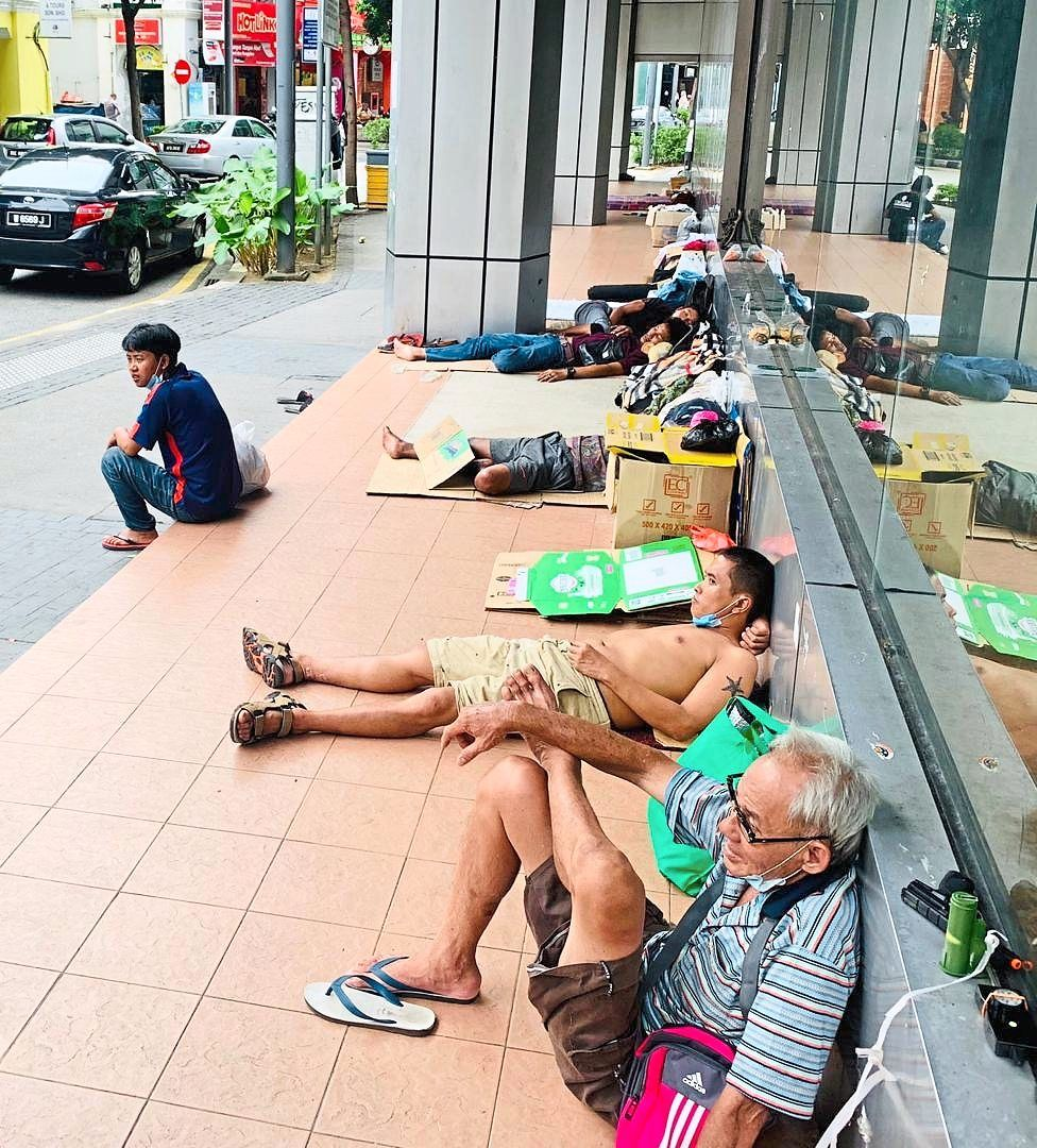 A group of people resting at this walkway along a row of shops in Jalan Petaling, Kuala Lumpur.