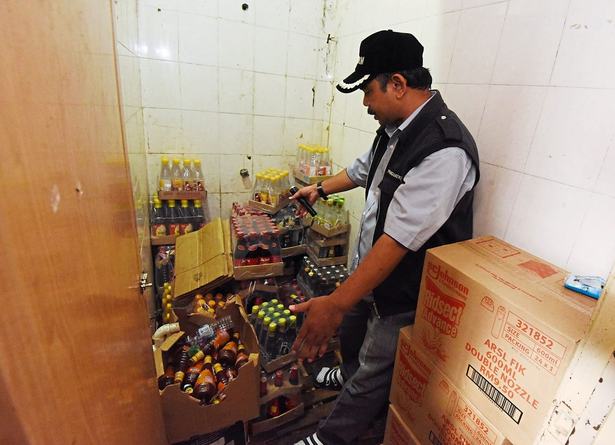 Mohd Wazir discovering the inappropriate use of a bathroom to store food products during the raid in one of the mini markets.