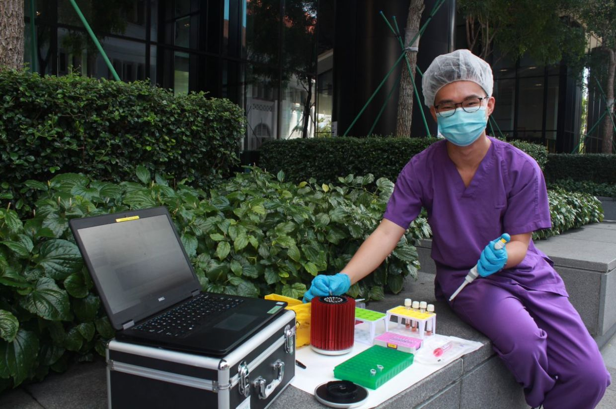 PhD candidate Wee Soon Keong with portable equipment that allows the test to be deployed in the community, outside of a lab setting, as a screening tool. - The Straits Times/ANN