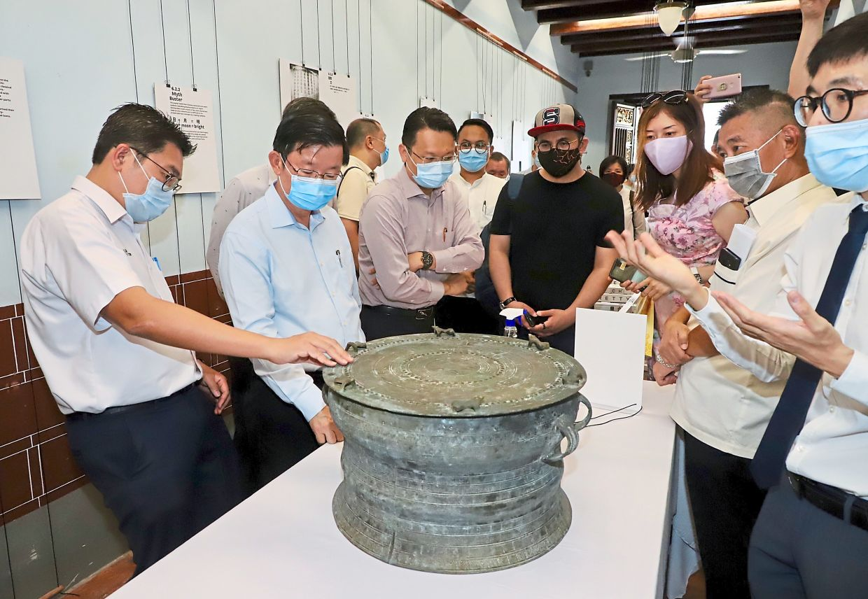Chow (second left) with Bayan Baru MP Sim Tze Tzin (left), Cheah Kongsi chairman Alan Cheah     (second right) and other guests checking out the Heger prehistoric drum as Sim Tze Wei (right) gives a briefing at the exhibition.