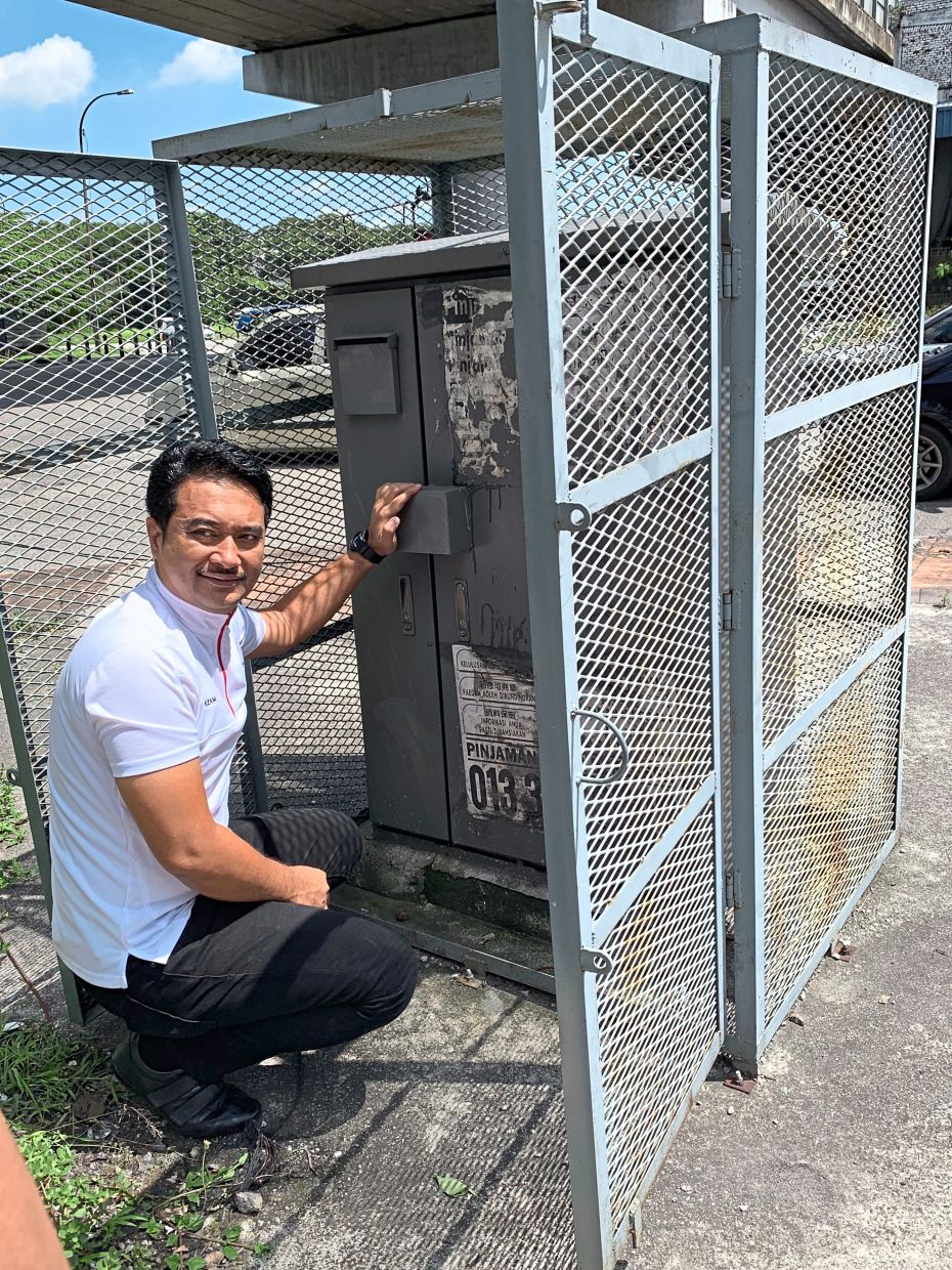 Azmizam showing a cage built for a feeder pillar box at Jalan Kem to deter vandals.