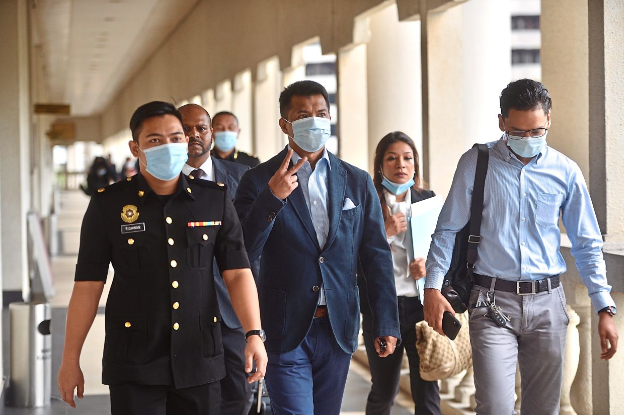 In hot water: Ibrahim (centre) arriving at the court for his trial.