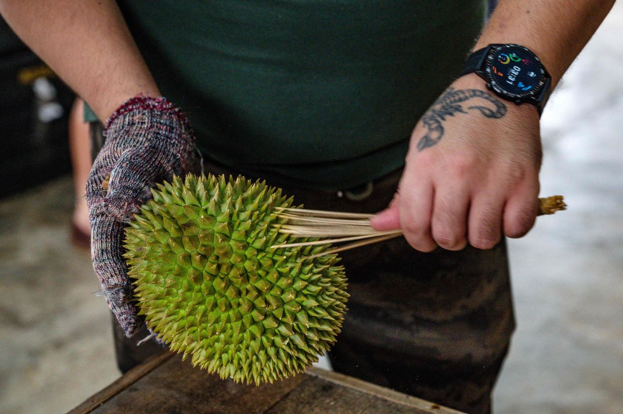 A worker cleaning a durian in Kuala Lumpur.