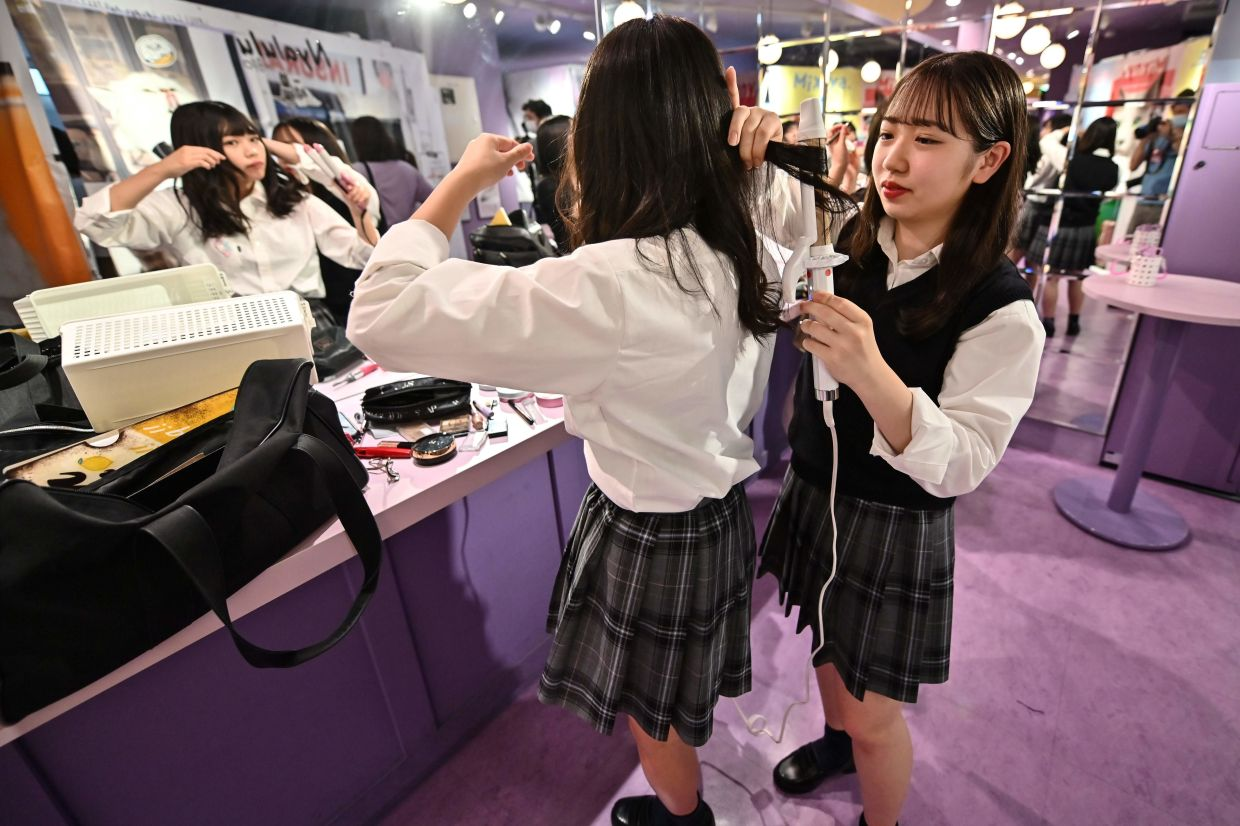 A pair of teenagers prepare themselves before using a Japanese style photo booth known locally as 'purikura'.
